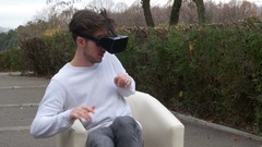Student sitting in an armchair in a park wearing virtual reality goggles vi.. Stock Footage