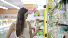 Young woman with cute daughter choosing a goods in grocery shopping mall Stock Footage