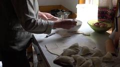 Senior woman hands prepare dumplings with curd in rural kitchen room. 4K Stock Footage