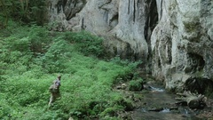 Tourist walking on a path through thick vegetation to reach the green Stock Footage