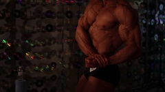 Deep tanned bodybuilder demonstrating large biceps, lack of body fat, fitness Stock Footage