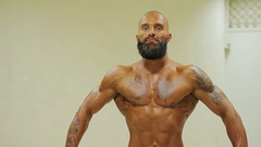 Deep tanned bodybuilder demonstrating strong body, showing triceps at sport club Stock Footage
