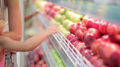 Woman and little girl choosing fruits during shopping at supermarket Stock Footage