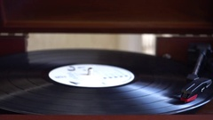 Turntable player,dropping stylus needle on vinyl of a spinning record playing. Stock Footage