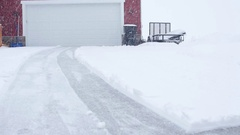 A man snowblowing his driveway during a blizzard Stock Footage