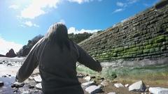 Woman walking on stones on beach Stock Footage