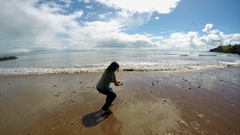 Woman throwing stones into sea Stock Footage