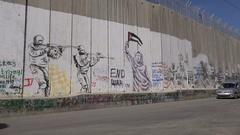 Traffic drives past graffiti art on separation barrier Bethlehem, West Bank Stock Footage