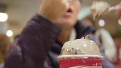 A couple eats a chocolate milkshake on a date Stock Footage