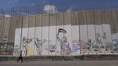 Man walks past murals painted on the separation wall West Bank Stock Footage