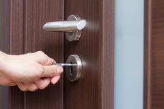 Hand unlocking house door Stock Photos
