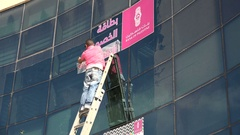 Worker applies advertising sticker to branch of Bank of Palestine Stock Footage