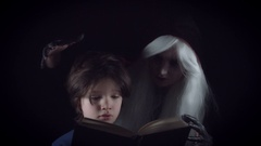 4K Horror Witch Appearing from Darkness and Child is Reading Story Book Stock Footage