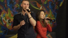 Guy and a girl singing in a karaoke club. Slow motion Stock Footage