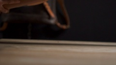 Craftsman putting a big roll of leather on the table in the workshop slow motion Stock Footage