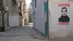 Narrow streets with murals on the walls in Aida permanent refugee camp Bethlehem Stock Footage