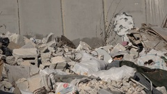 Closeup of garbage with the Israel - West Bank separation barrier in background Stock Footage