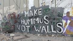 Ironic graffiti art, make hummus not walls, separation barrier West Bank Stock Footage