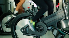Close-up - sports people pedaling on the exercise bicycle in the gym Stock Footage