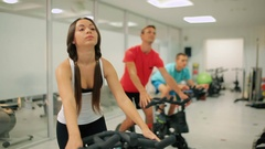 Two sportsmen and slim young woman trains breathing exercise on the simulator Stock Footage