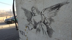 Famous angel graffiti mural made by international artist Banksy in West Bank Stock Footage