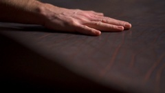 A craftsman sleeking a big piece of leather on the table slow motion Stock Footage