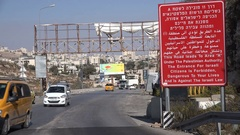 Traffic drives past warning sign for Israeli citizens in West Bank Stock Footage