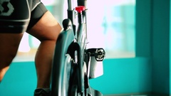Close-up - man scrolls the pedal on the exercise bike in the gym Stock Footage