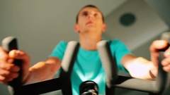 Attractive sportsman in blue T-shirt is cycling in the gym Stock Footage
