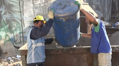 Palestinian UN workers empty garbage cans at separation wall West Bank Stock Footage