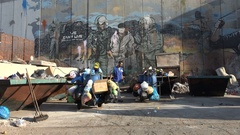 United Nations workers at garbage dump, graffiti art separation wall West Bank Stock Footage