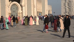 Colorful crowds walk past Hassan II mosque in Casablanca Stock Footage