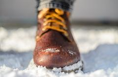 Snow melts on brown winter boots. Brown leather shoes in the snow. Legs in .. Stock Photos