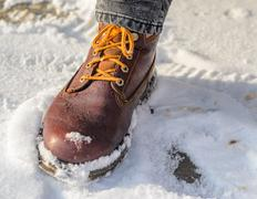 Brown leather shoes in the snow. Legs in the warmth concept Stock Photos