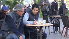Moroccan men do crossword puzzle in street cafe Casablanca Stock Footage