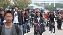Chinese students walk and cycle across the campus of Shanghai University Stock Footage