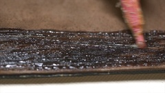 A craftsman applying the adhesive to the piece of leather in the workshop Stock Footage