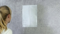 Piece of paper is hanging on a wall Stock Footage