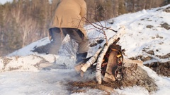 Man Stoking Fire in Winter Stock Footage