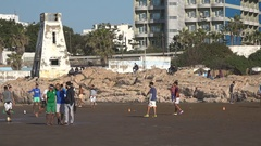 Morocco leisure activities, people play soccer (football) on the beach Stock Footage