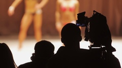 Professional operator filming female bodybuilding competition, camera crew Stock Footage