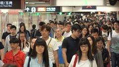 Huge crowds of people walk through a corridor in the metro (subway) of Hong Kong Stock Footage