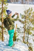 Young beautiful woman with snowshoes and mobile phone chill out in the forest Stock Photos