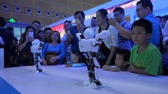 Chinese people watch dancing robots at a technology trade show in Shenzhen Stock Footage