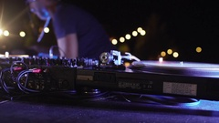 Caucasian DJ in blue t-shirt playing music at outdoor party at night pool party Stock Footage