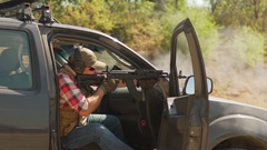 Caucasian male in cap plaid shirt and sunglasses firing airsoft gun sitting on Stock Footage