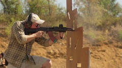 Adult Caucasian male in headphones and sunglasses firing airsoft gun behind Stock Footage