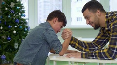 Father and son armwrestle on the table Stock Footage