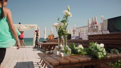 Man and women preparing decoration for wedding on terrace near sea on background Stock Footage