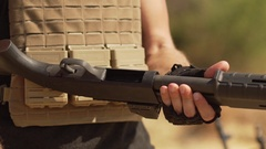 Man charging rounds in airsoft shotgun outdoors. Close up footage in slowmotion Stock Footage